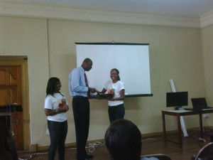Secretary Marie Benjamin presents items to Mr. Gibbs as President, Trisha Mitchell looks on.